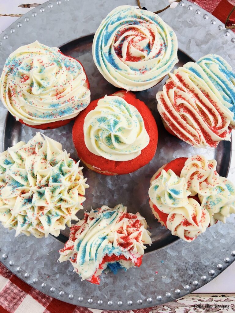 Another look at a plate full of the finished and decorated layered red white and blue cupcakes.