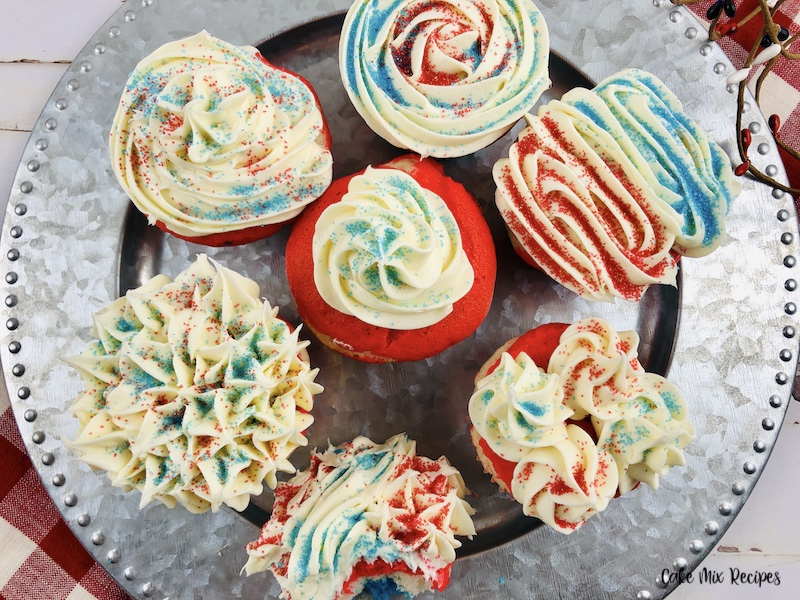 A plate full of the decorated layered red white and blue cupcakes ready to eat.
