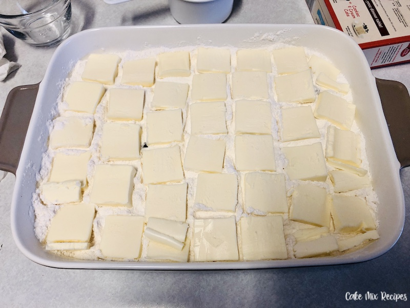 butter slices on top of the cake mix and blueberries.