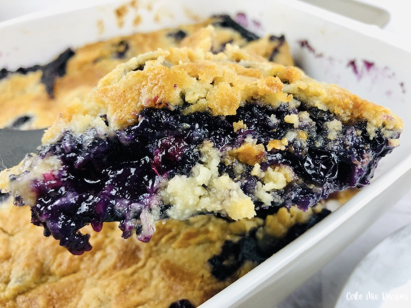 A scoop of the finished blueberry dump cake held up to the camera ready to serve.