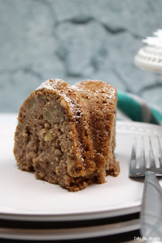 a close up of a slice of the recipe for apple bundt cake ready to eat.