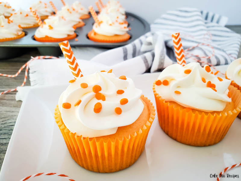 A close up view of two creamsicle cupcake treats ready to eat.